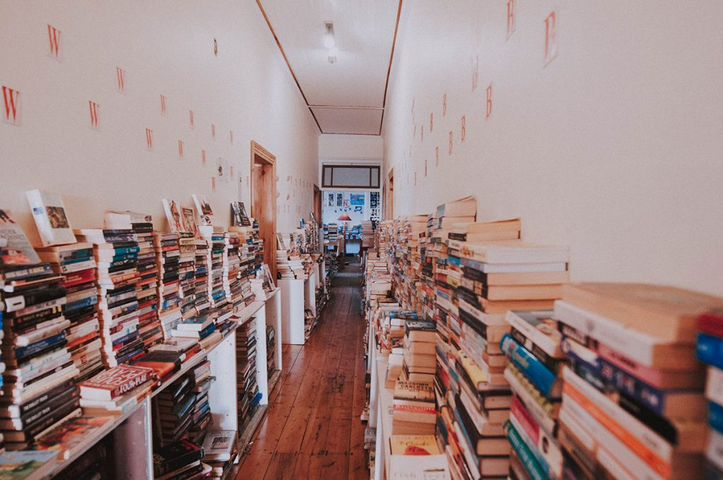 Books stacked against wall inside Bikini Beach bookshop