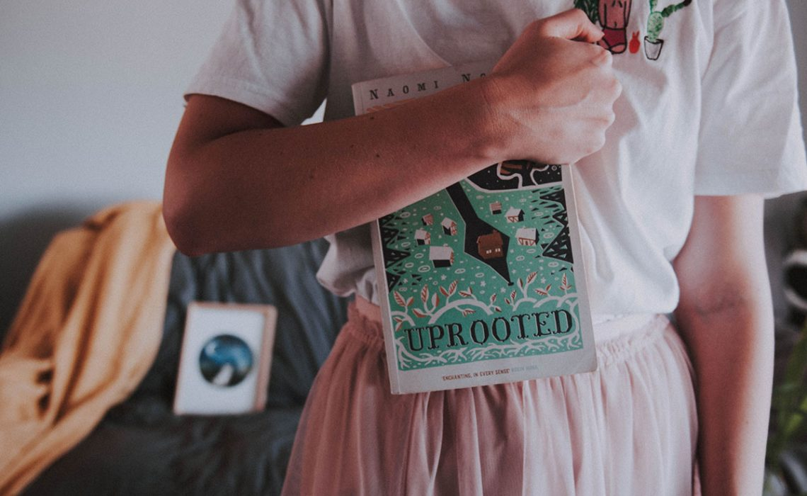 One girl holding a book, Uprooted by Naomi Novik.