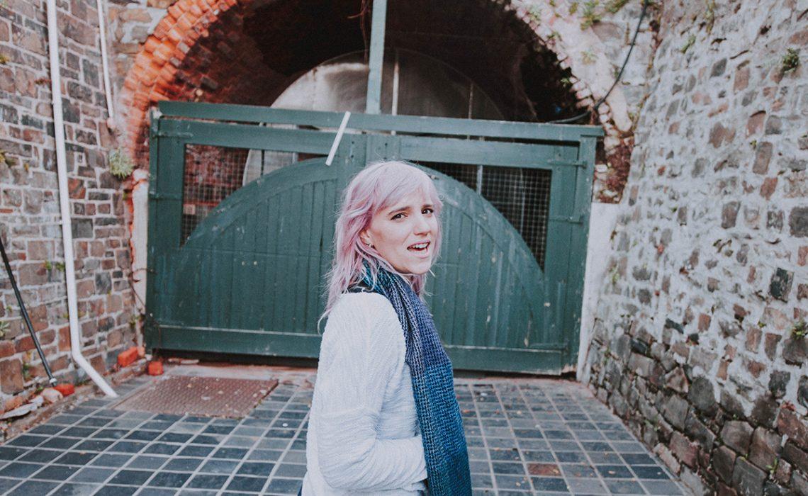 Girl with purple hair, standing in front of large door.