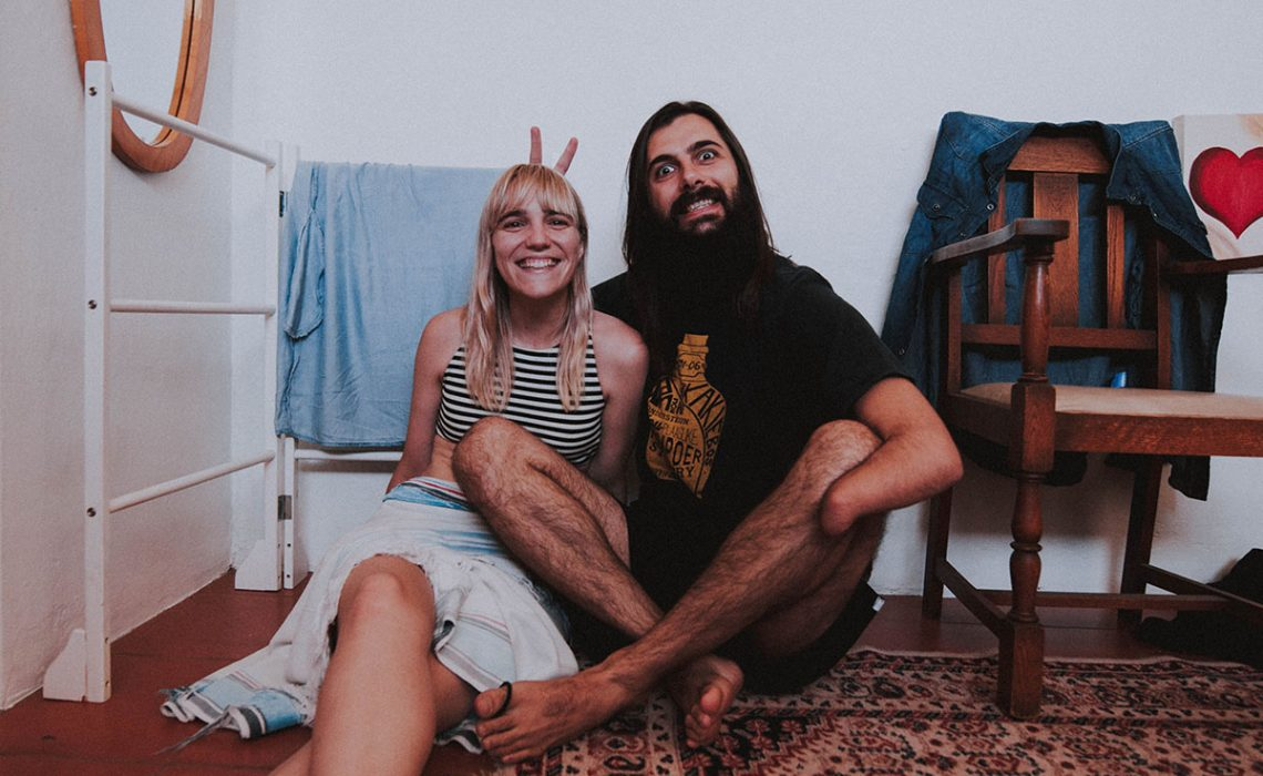 Blonde girl sitting next to bearded boy.