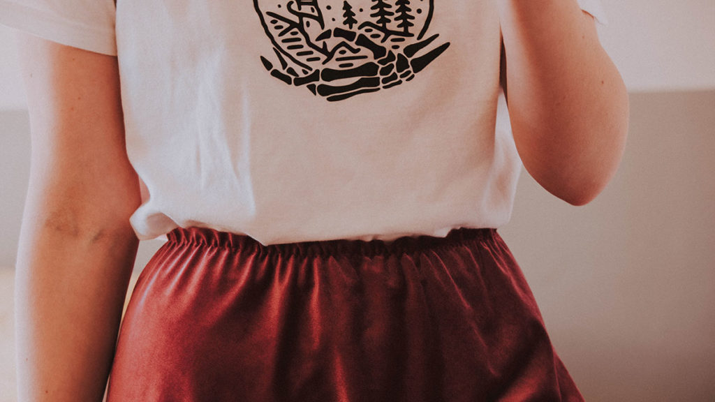 Waist of girl with skirt and tucked in white t-shirt.