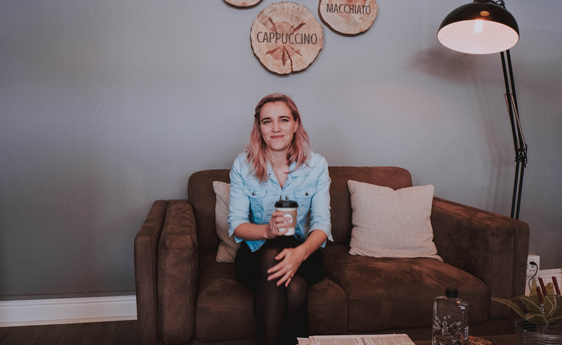 Girl sitting on couch, with coffee in hand.