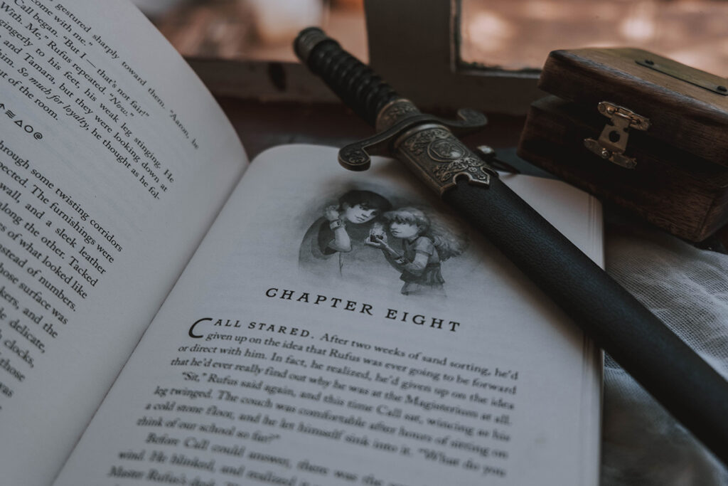 The Iron Trial open at Chapter Eight with dagger on top of it.