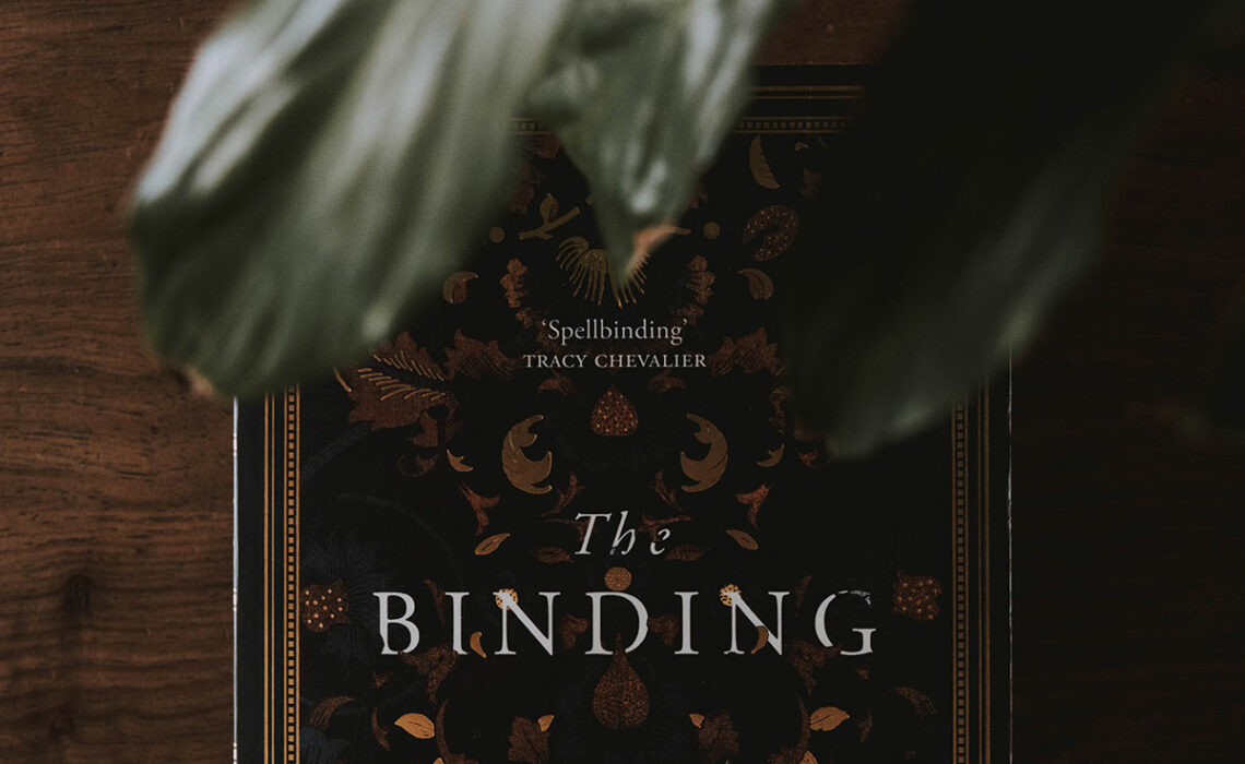 The cover of Bridget Collins' book, The Binding with a leaf over it.