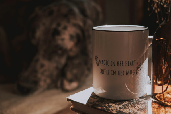 Mug with written words printed on it. Magic in the heart. Coffee in the mug.