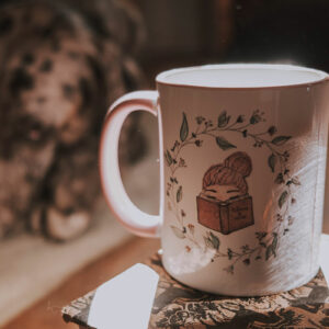 Magical mug from the Alex+A collection. Girl with pink hair, reading a book. Floral wreath around her.